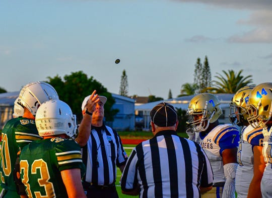 The referee begins the coin toss.