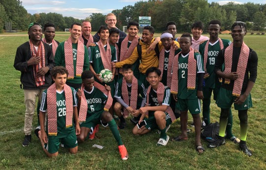 Winooski's Lek Nath Luitel (with ball) poses with his team after their win against Richford in which he scored his 100th career goal.