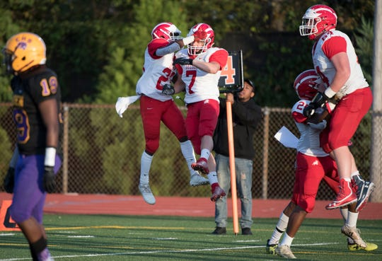 Delsea's Tyvon Dawkins, center left, celebrates with Delsea's Jared Schoppe after Dawkins scored a touchdown during the 1st quarter of the football game between Delsea and Camden played in Camden on Friday, September 27, 2019.