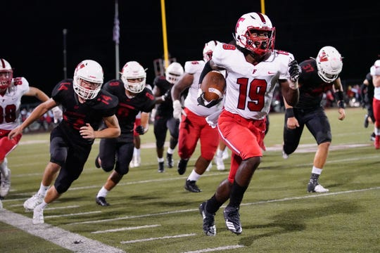Fairfield slotback Jaydan Mayes (19) races down the sideline during Friday night's varsity football match at Lakota West. Fairfield won the game 33-7.
