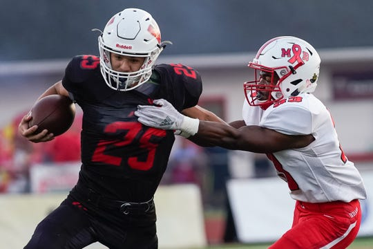 Lakota West quarterback Mitch Bolden (25) evades Fairfield safety Nykel Bell (33) during Friday night's varsity football match at Lakota West. Fairfield won the game 33-7.