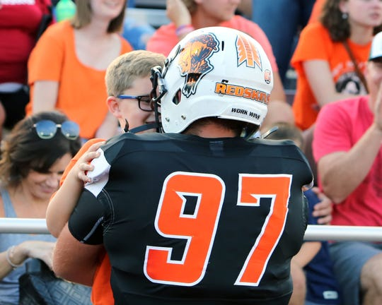 Anderson defensive lineman Tanner Shirley, No. 97,  hugs his brother Aiden at the game between Anderson and Withrow high schools.