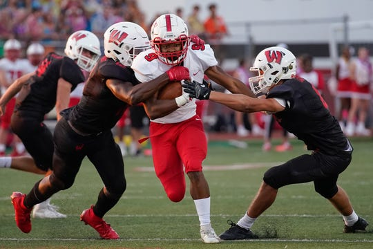 Fairfield running back JuTahn McClain (9) makes contact with Lakota West linebacker Daved Jones (12) and defensive back Truman Mason (8) during Friday's varsity football match at Lakota West. Fairfield won the game 33-7.