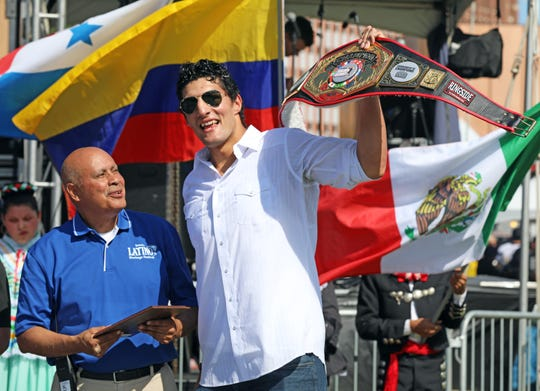 Joe Gonzalez presents boxing champion Antonio Rodriguez-Mireles with the 2019 Latino Achievement Award during the Iowa Latino Heritage Festival in the Western Gateway Park on Saturday, September 28, 2019 in Des Moines featuring artist displays, cultural booths, children's activities, Latin American cuisine, live music, folkloric dance, and much more at the weekend event.