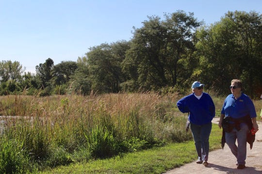 Judy Davis walk alongside Debbie Scott during Saturday's NAMIWalks Iowa event. Davis said she's a former community mental health nurse, who retired into working at NAMI for years and now move to other community service work.
