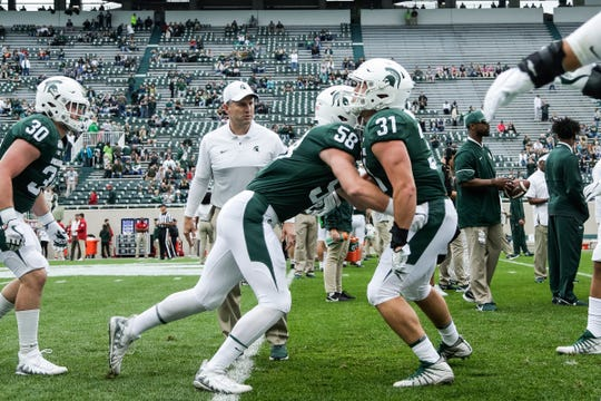 Michigan State offensive lineman Spencer Brown (58) and  linebacker Edward Warinner (31) warm up before the Indiana game at Spartan Stadium in East Lansing, Saturday, Sept. 28, 2019.
