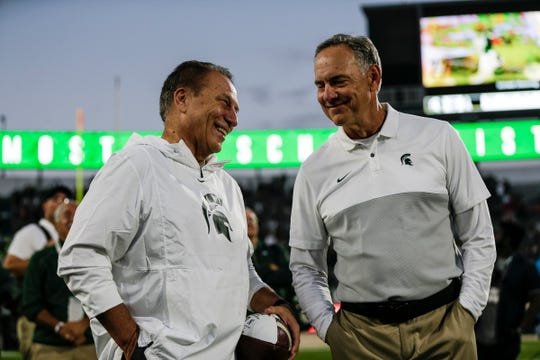 Mark Dantonio, right, talks to basketball coach Tom Izzo, as they celebrate the 40-31 win over Indiana, and Dantonio's MSU record for wins.
