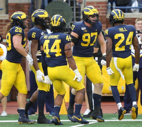 Michigan Michigan Wolverines defensive lineman Aidan Hutchinson celebrates with teammates after a stop during the first half of U-M's 52-0 win on Saturday, Sept. 28, 2019, at Michigan Stadium.