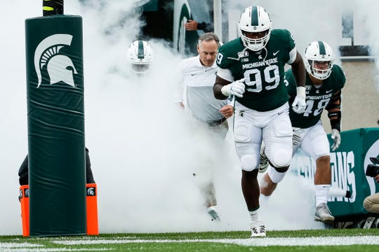 Michigan State defensive tackle Raequan Williams (99) and head coach Mark Dantonio take the field before the Indiana game at Spartan Stadium in East Lansing, Saturday, Sept. 28, 2019.