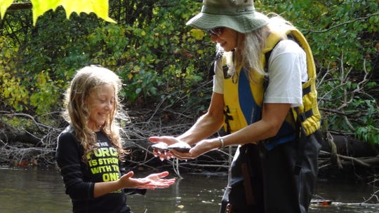 A Friends of the Rouge member shows a child volunteer two river mussels, an indicator of healthy water quality.
