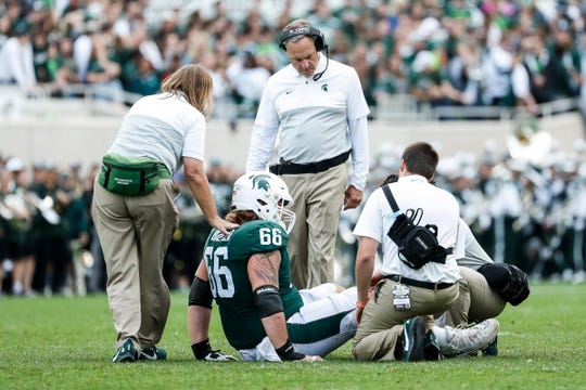 Michigan State head coach Mark Dantonio checks on offensive lineman Blake Bueter during the first half against Indiana at Spartan Stadium in East Lansing, Saturday, Sept. 28, 2019.