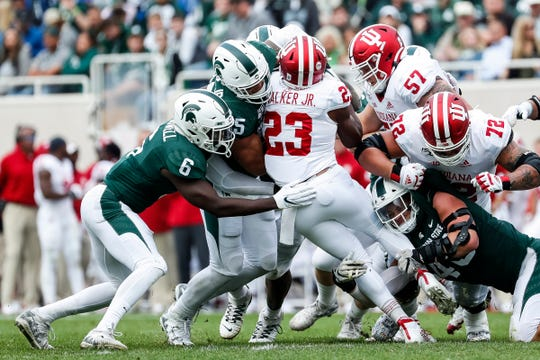 Michigan State safety David Dowell (6), linebacker Joe Bachie (35) and end Kenny Willekes (48) try to stop Indiana running back Ronnie Walker Jr. during the first half at Spartan Stadium in East Lansing, Saturday, Sept. 28, 2019.