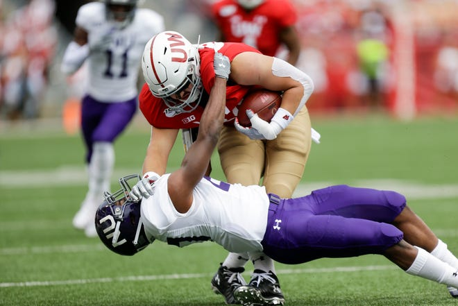 Northwestern defensive back Coco Azema (27) tackles Wisconsin tight end Jake Ferguson (84) during the first half on Saturday.
