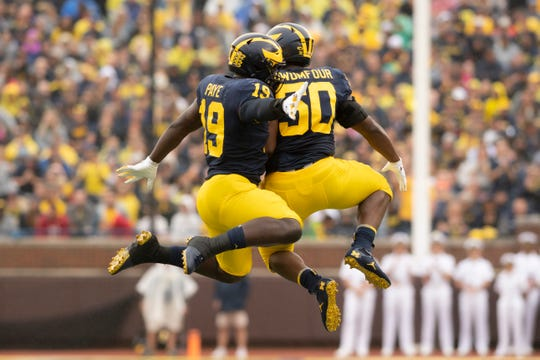 Michigan wide receiver Mike Sainristil, left, and defensive lineman Michael Dwumfour celebrate after a sack in the second quarter.