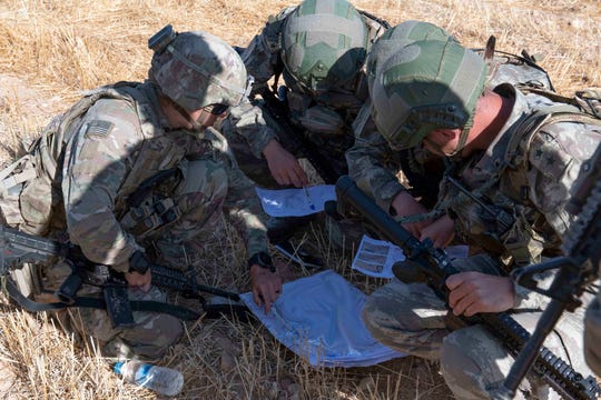 "U.S. and Turkish military forces go over a map in preparation of their second joint ground patrol inside the so-called ""safe zone"" in northeast Syria near the border with Turkey on Sept. 24."