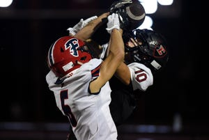 Livonia Churchill wide receiver Ethan Lebar, right, and Livonia Franklin defensive back Tyler Whisman battle for the ball during the second overtime on Friday.