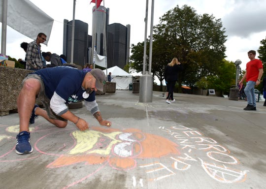 """Clayton Monte, of Livonia, colors in a chalk caricature of his brother, Jarrod """"Skull Ape"""" Clayton, a father of two boys, who died of suicide Dec. 2, 2018."""