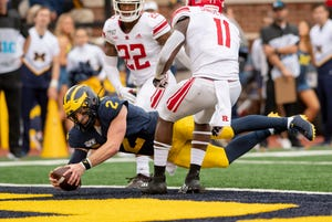 Michigan quarterback Shea Patterson dives into the end zone for one of his three rushing scores on Saturday.