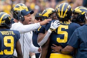 Michigan offensive coordinator Josh Gattis and wide receiver Tarik Black congratulate quarterback Joe Milton after Milton ran for a touchdown in the fourth quarter.