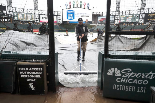 Members of the Chicago White Sox grounds crew remove rainwater off the tarp during a rain delay between the White Sox and Tigers on Friday.