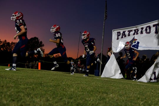 Heritage Hills' Caleb Fakes (24), left to right, Jordan Mitchell (88), Trenton Hill (5) and Kort Schader (2) rush onto the field to take on the Gibson Southern Titans at Patriot Field in Lincoln City, Ind., Friday night, Sept. 27, 2019. The Patriots defeated the Titans, 49-14.