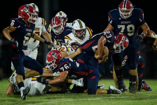 Heritage Hills' Phoenix Rodgers (23) pushes his way into first down against the Gibson Southern Titans in the first quarter at Patriot Field in Lincoln City, Ind., Friday night,  Sept. 27, 2019. The Patriots defeated the Titans, 49-14.