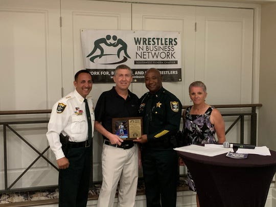 (From left) Lee County Sheriff Carmine Marceno, Riverdale wrestling coach Kris Hayward, Lt. Angelo Vaughn and Kim Freis pose Saturday after Hayward was presented with the Gary Freis Excellence in Coaching award named after the late Fort Myers wrestling coach at the Wrestlers in Business Network fundraiser at The Forest Country Club.