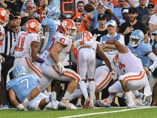 Clemson safety Nolan Turner (24),  James Skalski (47), and defensive lineman Xavier Thomas (3) stop North Carolina quarterback Sam Howell on a two-point conversion attempt during the fourth quarter  at Kenan Memorial Stadium in Chapel Hill, North Carolina Saturday, September 28, 2019.