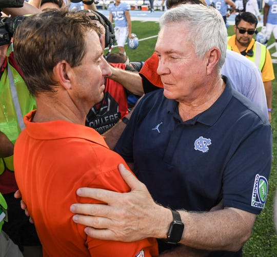 Clemson Head Coach Dabo Swinney and North Carolina Head Coach Mack Brown meet after the Tigers 21-20 win after the game  at Kenan Memorial Stadium in Chapel Hill, North Carolina Saturday, September 28, 2019.