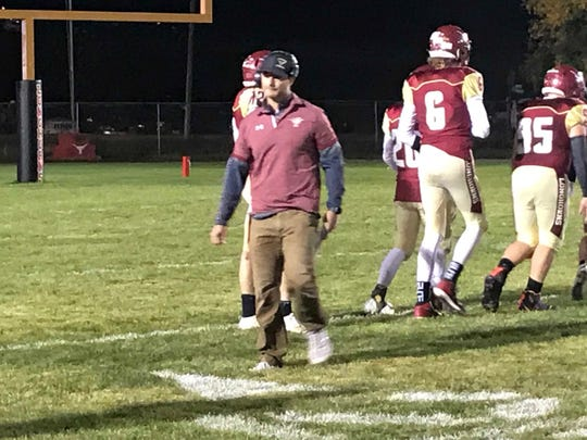 Fort Benton head coach Jory Thompson, center, leaves his team's huddle after a timeout in the first half of his team's 46-35 win over Great Falls Central Friday night at Lenington Memorial Field.