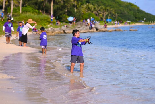 Young anglers cast their lines into the waters off the shores of the War in the Pacific National Historical Park Asan Beach Unit .