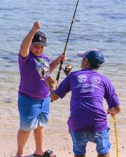 Young angler Jaythan Esperon, 11, hauls up a trigger fish he caught si the catch could be measured and recorded by Jun Ducusin, a fisheries technician with the Department of Agriculture Division of Aquatic Wildlife and Resources, during the Fishing Derby for Kids at the War in the Pacific National Historical Park Asan Beach Unit on Saturday, Sept. 28, 2019.
