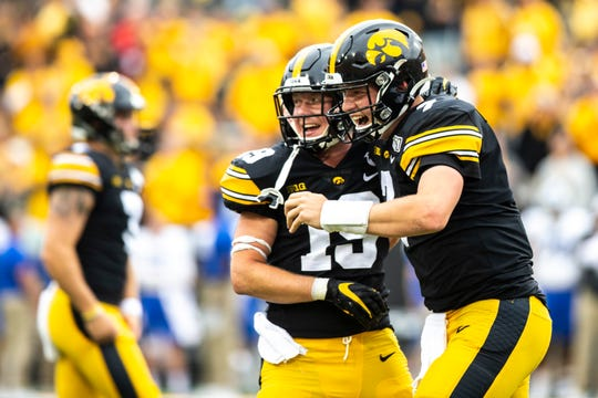 Spencer Petras (7) has become a locker-room favorite in Iowa City, so it was no wonder that teammates (like Max Cooper, left) were excited when he ran a QB sneak for a touchdown against Middle Tennessee State.