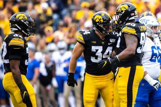 Iowa linebacker Kristian Welch (34) celebrates with Iowa defensive lineman Cedrick Lattimore (95) after his sack during a NCAA non conference football game between the Iowa Hawkeyes and Middle Tennessee State, Saturday, Sept., 28, 2019, at Kinnick Stadium in Iowa City, Iowa.