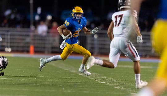 Carmel High School junior Colton Parker (22) looks for a route upfield during the first half of an IHSAA high school football game at Carmel High School, Friday, Sept. 27, 2019.
