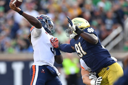 Virginia Cavaliers quarterback Bryce Perkins (3) throws under pressure from Notre Dame Fighting Irish defensive lineman Adetokunbo Ogundeji (91) in the third quarter at Notre Dame Stadium.