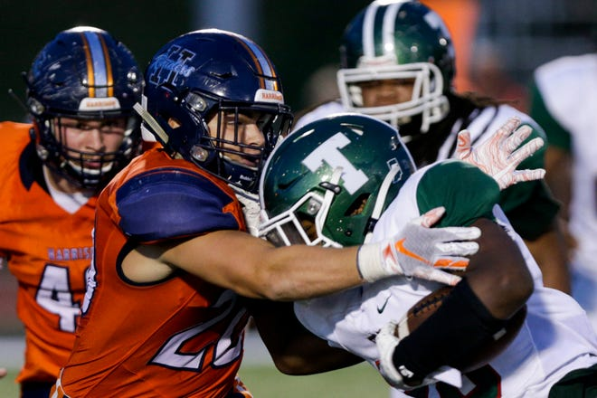 Harrison linebacker Quinton Wood (20) tackles Arsenal Tech's Jayden Elliott (28) during the second quarter of an IHSAA football game, Friday, Sept. 27, 2019 at Harrison High School in West Lafayette. Harrison won, 28-0.