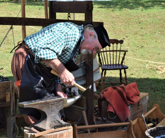 A reenactor smiths a hook in the village at the Frontier Spirit 1799 event Saturday. The two-day event features reenactors in period clothing, demonstrating pioneer life.