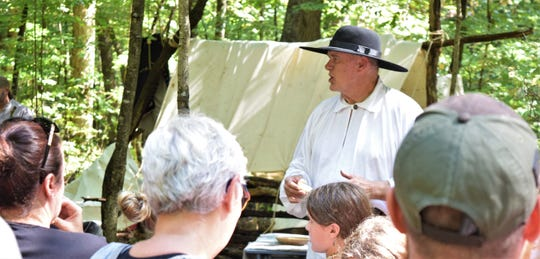 Gary Montgomery, as a captain of a group of woodsmen, instructs his guides to get their guests to the next stop on the Drama Trail at the Frontier Spirit 1799 event Saturday. The two-day event features reenactors in period clothing, demonstrating pioneer life.