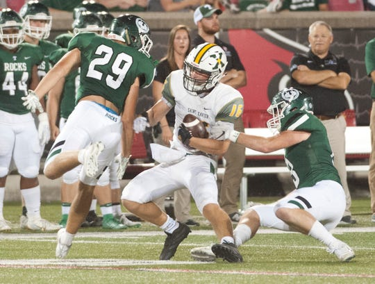 Trinity linebacker Jack Dingle, left, and Trinity defensive back Brandon Stearman, right, try to deny St. Xavier wide receiver Grant Goodman any more yards.