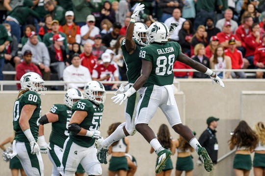 Michigan State's Elijah Collins, left, celebrates his touchdown with teammate Trenton Gillison Indiana's during the first quarter on Saturday, Sept. 28, 2019, in East Lansing.