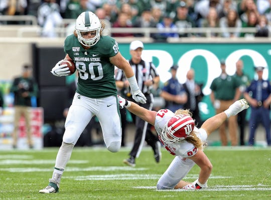 Sep 28, 2019; East Lansing, MI, USA; Michigan State Spartans tight end Matt Seybert runs through  the table of Indiana Hoosiers defensive lineman Michael Ziemba (87) during the first quarter of a game at Spartan Stadium. Mandatory Credit: Mike Carter-USA TODAY Sports