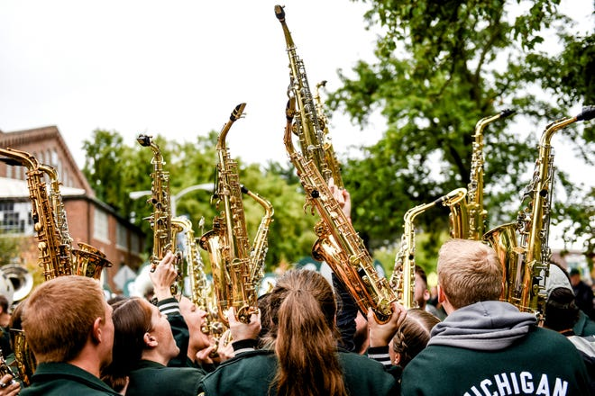 Members of the MSU alumni band hold their instruments in the air before the Spartans homecoming game against Indiana on Saturday, Sept. 28, 2019, in East Lansing.
