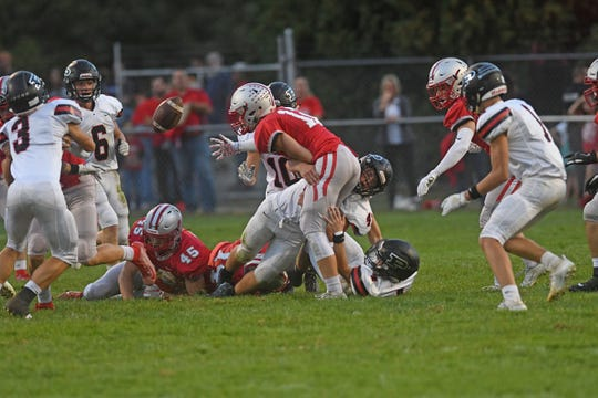 Shelby's Grant Gossum loses the handle on the football Friday night as he is hit by a trio of Marion Pleasant defenders.