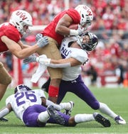 Northwestern's Travis Whillock wraps up Wisconsin's Jonathan Taylor.