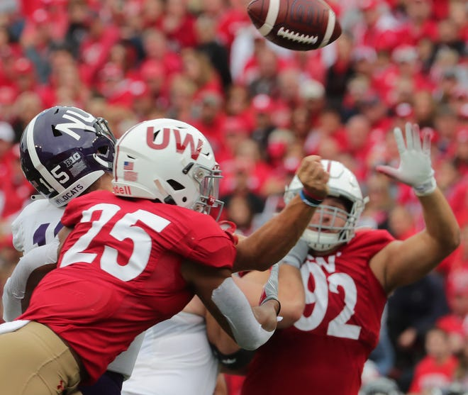 Wisconsin safety Eric Burrell hits Northwestern quarterback Hunter Johnson to force a fumble in the third quarter.
