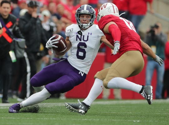 Northwestern running Drake Anderson slips while try to make a move on Wisconsin safety Collin Wilder. Wilder and John Torchio did a creditable job while Eric Burrell and Reggie Pearson sat out the first half Saturday.