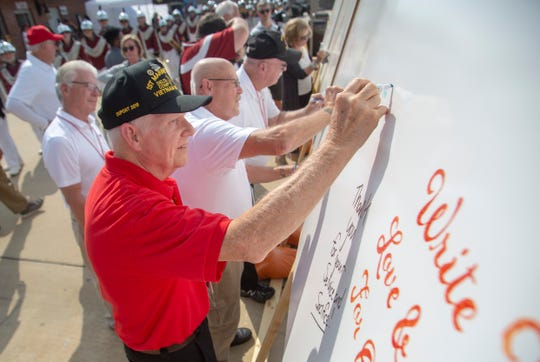 A few Vietnam veterans signs a whiteboard to support the troops during military appreciation day at Veterans Memorial Stadium.