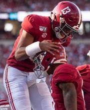 Alabama quarterback Tua Tagovailoa (13) celebrates with wide receiver DeVonta Smith (6) after connecting for their fish touchdown together against Ole Miss at Bryant-Denny Stadium in Tuscaloosa, Ala., on Saturday September 28, 2019.