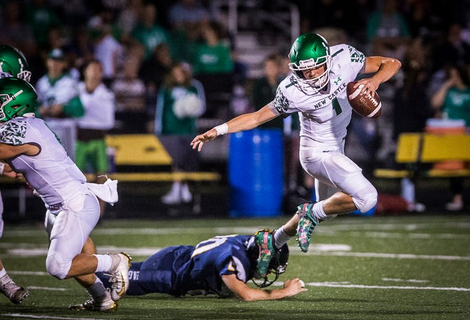 New Castle's William Grieser struggles against Delta's defense during their game at Delta High School Friday, Sept. 27, 2019.